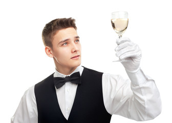 Young waiter looking at the glass filled with white wine