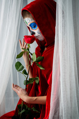 Day of the dead girl with sugar skull makeup holding red rose