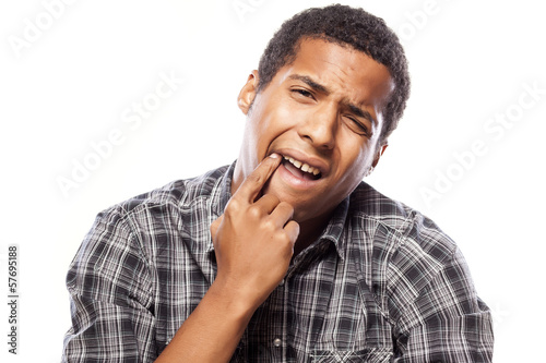 African man shows with his finger on the tooth that hurts him