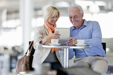 Smiling couple using digital tablet at cafe table
