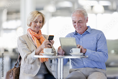 Smiling couple using cell phone and digital tablet at cafe table