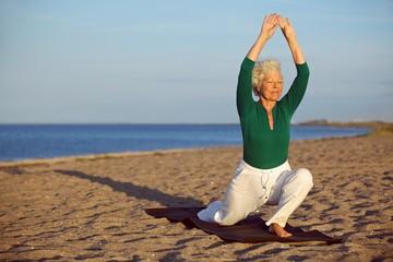 Senior woman stretching on the beach