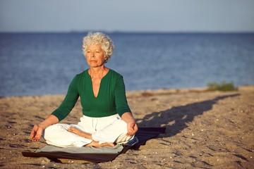 Elderly woman on beach meditating by ocean