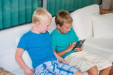 Two boys playing on touchscreen tablet computer