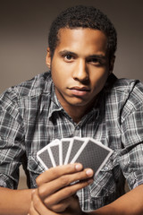 serious dark-skinned young man holding playing cards