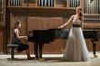 Leinwandbild Motiv Woman pianist plays piano and singer stands next