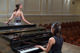 Fototapety Woman pianist sits at piano and singer stands next