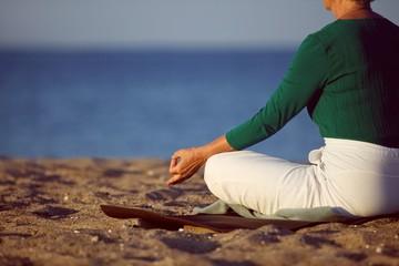Mature woman doing yoga on sandy beach