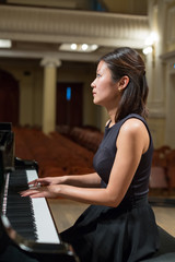 Woman pianist sits at piano in empty concert hall