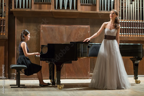 Woman pianist plays piano and singer stands next