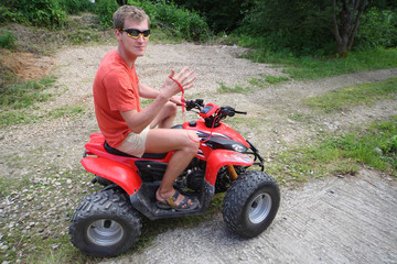 man in sunglasses on quad bike ride on impassability