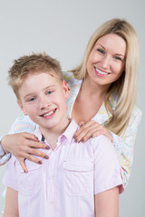 smiling mother hugging young son with disheveled hair