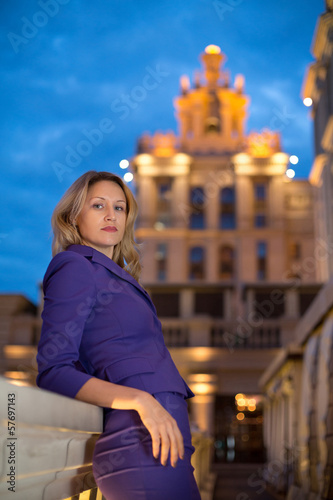 Beautiful girl is leaning on parapet in evening city