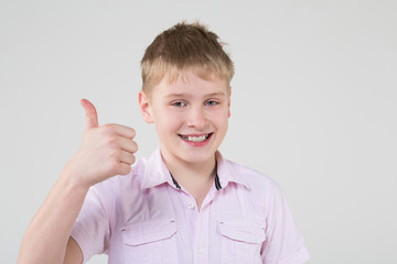 The boy in a pink shirt making a thumbs up