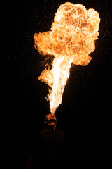 Fakir breathes spurts of fire in the dark