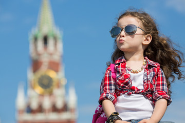 Little girl in stylish dress and sunglasses sitting near Kremlin