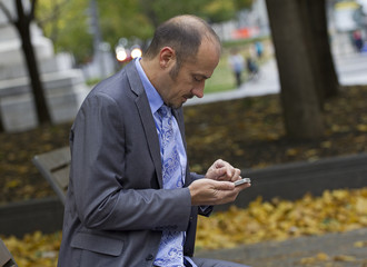 business man texting in the park