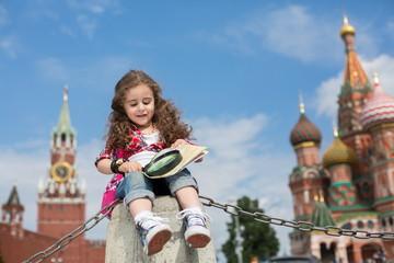 The little girl sitting on concrete near the Kremlin