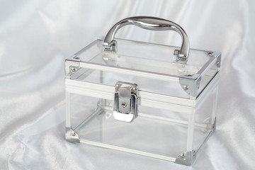 Transparent chest with chrome details on satin cloth