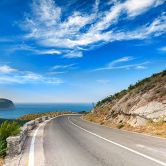 Turn of mountain highway with dramatic blue sky and sea