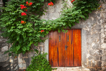 Red wooden gate in old stone wall with decorative flowers