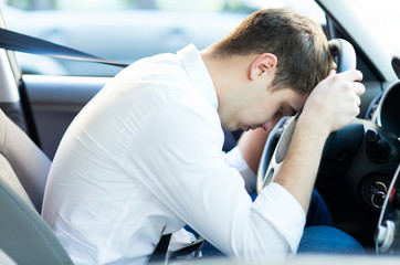 Exhausted driver resting on steering wheel