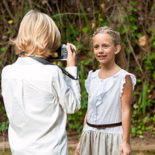 Boy taking picture of cute girl outdoors.