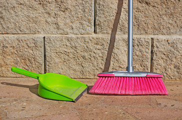 pink broom and green shovel