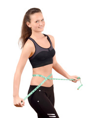 Fit girl measuring her waist with a measuring tape in inch