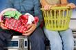 Couple With Laundry Baskets Sitting On Washing Machines