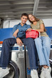 Couple With Laundry Basket Sitting On Washing Machines