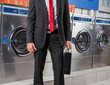 Businessman Holding Suitcase In Laundry