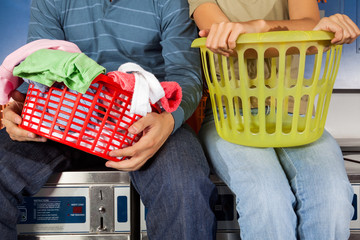Couple With Laundry Baskets Sitting On Washing Machines