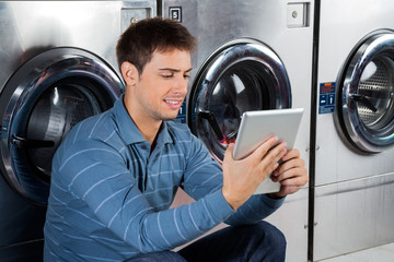 Man Using Digital Tablet At Laundry