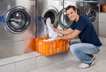 Young Man Putting Clothes In Washing Machine