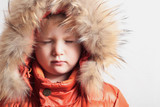 Child in fur hood and orange winter jacket