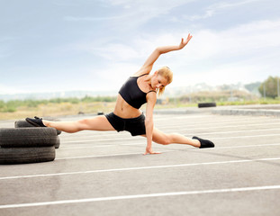 Portrait of Young Sporty Woman Doing Stretching Exercise.
