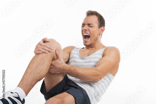 Man screaming from a pain in his knee. While isolated on white