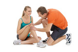 Handsome trainer checking woman knee.