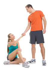 Fit man helping attractive woman to rise.