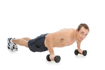 Fit man pushing up with dumbbells.