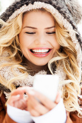 Woman in winter clothing texting
