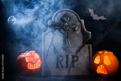 Halloween pumpkins with moon, tombstone and bat on misty night.