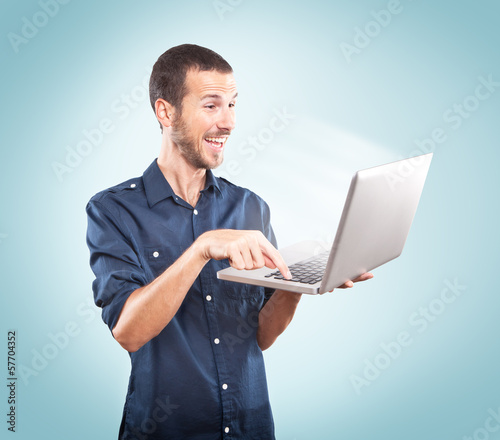 Young man happy holding a laptop