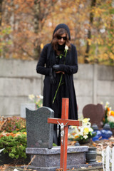 Grieving woman at cemetery in autumn