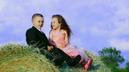 Two children in love on a haystack