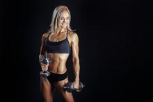 Athlétique jeune femme faisant une séance d'entraînement de fitness avec haltères sur bl
