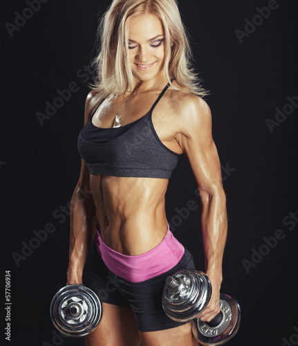Sexy athletic blonde girl with dumbbells on smoke background
