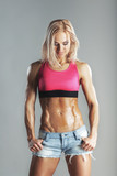 beautiful young sporty muscular woman looking on her abs