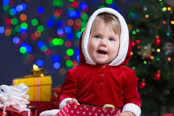baby girl dressed Santa Claus at Christmas tree